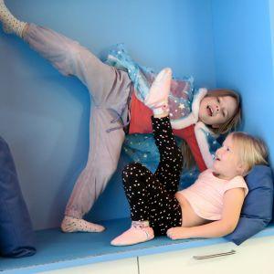 Haukiluoman päiväkodin kaksi tyttöä leikkii olokolo-syvennyksessä.