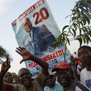 Felix Tshisekedin kannattajat huutavat ja kannattelevat suurta kylttiä, jossa on Tshisekedin kuva.