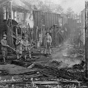 Mustavalkoinen valokuva sotilaista rakennuksen hiiltyneiden jäänteiden ääressä.