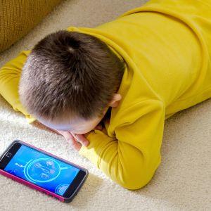 lapsi katsoo kännykkää lattialla