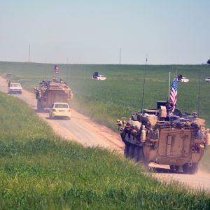 Kaksi panssariajoneuvoa ajaa tiellä Yhdysvaltain liput liehuen. Kauempana pellom keskellä näkyy valkoisia pick up -autoja.