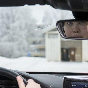 Nuori nainen ajaa autoa ja katsoo taakseen peilistä.