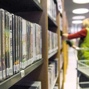 Kirjaston hylly, taustalla nainen hyllyttää kirjoja
