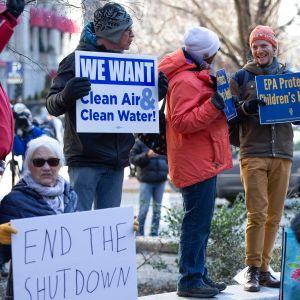 Kuvassa talviasuihin pukeutuneita työntekijöitä pitämässä kylttejä, joissa vaativat hallinnon sulun lopettamista.