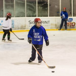 Lapsia pelaamassa jääkiekkoa.