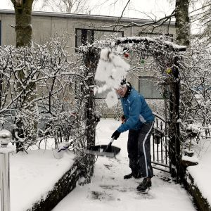 Mies tekee lumitöitä.