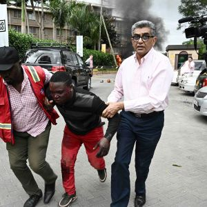 Haavoittunutta miestä talutetaan pois räjähdyspaikalta.