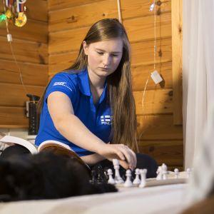 Anastasia Nazarova pelaa shakkia huoneessaan Savitaipaleella kissansa kanssa.