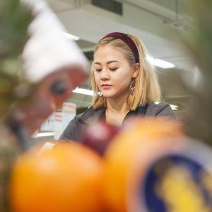 kauppias asettelee hedelmiä