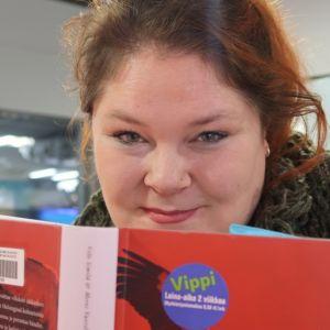 Tiina Koskinen kurkistaa kirjan takaa