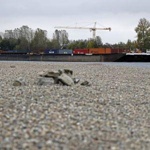 Etualalla hiekkaa, taaempana näkyy pitkä kuljetusalus, jolla on kontteja kyydissään.