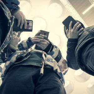 Nuoret käyttävät kännyköitä kauppakeskuksessa.