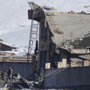 Joukko univormupukuisia miehiä seisoo osittain romahtaneen rakennuksen raunioilla. Taustalla näkyy lumista maisemaa.