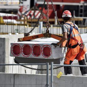 rakennusmies ja betonipalkki