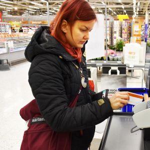 Kuvassa asiakas maksaa kaupan itsepalvelukassalla