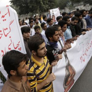 Miehiä mielenosoituksessa, julisteessa kuva Asia Bibistä hirttoköydessä.
