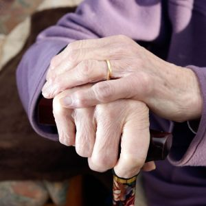 Vanhukset kädet kävelykepin päällä