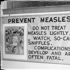 Mustavalkoinen kuva julisteesta, jossa on kuvia perheistä ja varoitus turkarokon hengenvaarallisista kompikaatioriskeistä.
