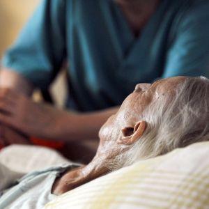 Hoitaja pitää vanhusta kädestä