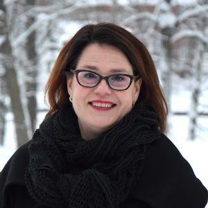 Nainen lähikuvassa taustallaan talvinen maisema