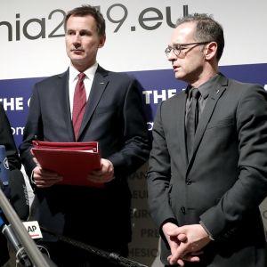 Ministerit pitävät tiedotustilaisuutta. Ranskan ulkoministeri puhuu mikrofonirykelmälle. Britannian ulkoministerillä on kädessään punainen kansio.