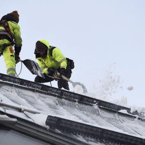Lumenpudottajia työssään Kiasman katolla Helsingissä 14. tammikuuta.
