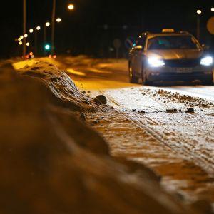 Henkilöauto kulkee lumisella ja liukkaalla tiellä.