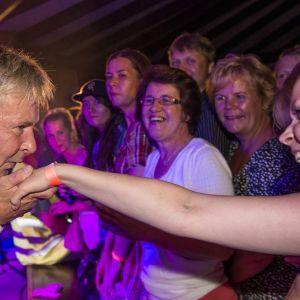 Matti Nykänen suutelee yleisössä olevan naisen kämmenselkää.