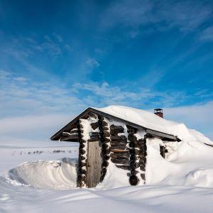 Moni lähtee lappiin upeiden luontokuvien perässä. Kuvassa lumen peittämä hirsimökki Kevolla.