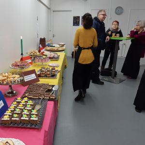 Pitkä pöytä, jossa on tarjolla erilaisia leivonnaisia. Ihmisiä seisoo kahvilla.