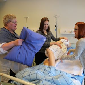 Lehtori opastaa lähihoitajaopiskelijoita Koulutuskeskus Salpauksen vuodeosastoluokassa.