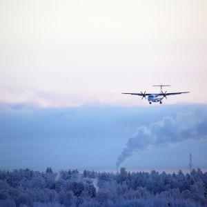 Norran lentokone laskeutuu Kemi-Tornion lentokentälle talvisäässä, taustalla savupiipuista nousevaa savua.