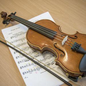 Lapsen viulu nuottipaperin päällä.