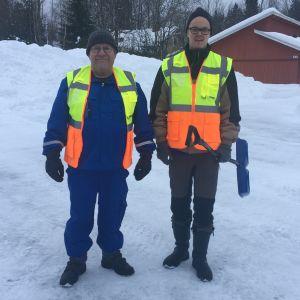 Kaksi miestä poseeraa huomioliivit päällä lumisella parkkipaikalla Pyhtäällä.