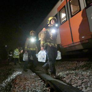 Pelastustyöntekijät kantavat suuria vesipulloja junan vierellä.