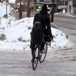 Pyöräilijä kyyditsee lasta talvisissa olosuhteissa Helsingissä