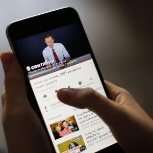 Venäläinen nainen katselle YouTube-videota kännykällä.