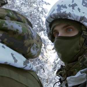 Varusmies pukeutunut kypärämyssyyn talvipakkasessa lumisessa metsässä