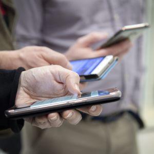 Nainen ja kaksi miestä katsovat puhelimistaan sosiaalista mediaa.