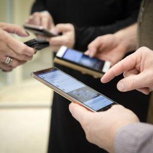 Kaksi naista ja kaksi miestä puhelimilla sosiaalisessa mediassa.