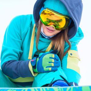Nuori nainen laskettelusukset jalassa pitelee polveaan kaaduttuaan.