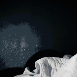 Ihminen pyörii sängyssä pimeässä makuuhuoneessa ja murehtii.