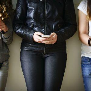 Nuoria käyttämässä kännyköitään.
