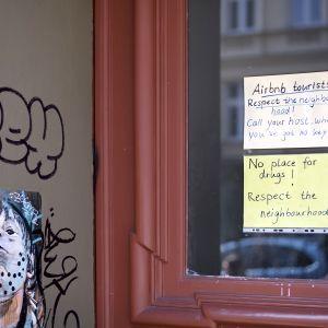 Turisteille kirjoitettu viestilappu kerrostalon rapun ovessa.