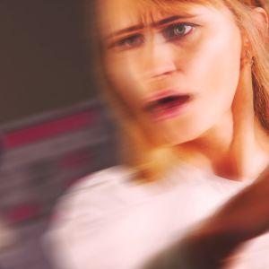 Vihainen nainen läpsäisee toista ihmistä joka ei näy kuvassa.