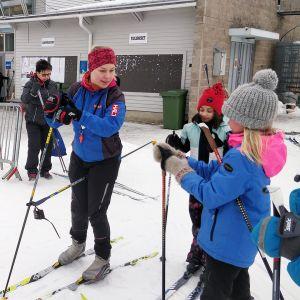 Vilja Välimäki auttaa koululaisia hiihtovälineiden pukemisen kanssa.