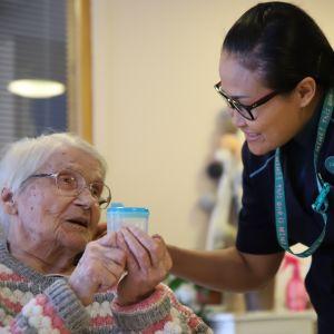 Lähihoitaja Amnuay Jalonen tarjoaa ikäihmiselle juotavaa.