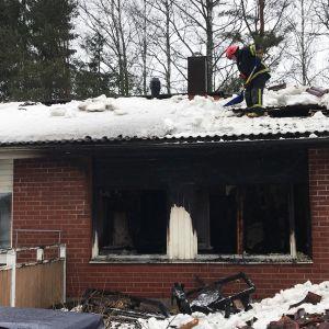 Palomies lapioi lunta palaneen rivitaloasunnon katolla