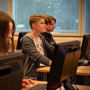 Ysiluokkalaiset Veera Takala (vas.), Markus Kinnunen ja Jaakko Hautaniemi tutkimassa tarjolla olevia työpaikkoja Jaakko Ilkan koulussa Ilmajoella.