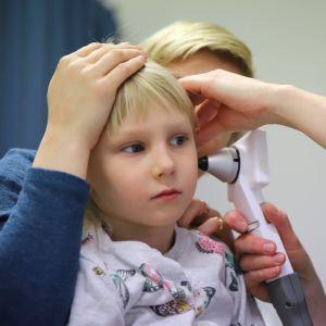Hoitaja tutkii lapsen korvaa kameran avulla.
